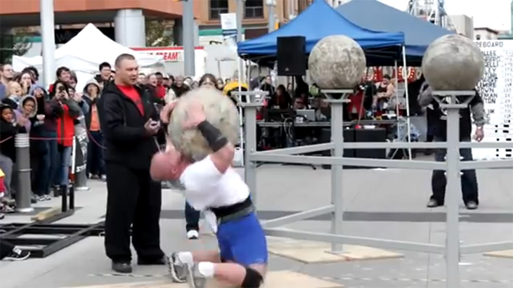 重い巨石を持ち上げる競技中に巨石に潰されてしまう男性の動画。