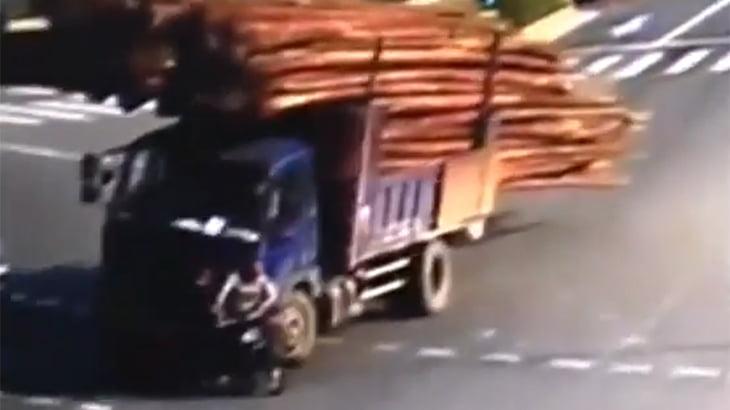 木材を積んだトラックが転倒。その下敷きとなる男性の動画。