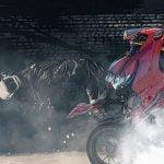 2人乗りバイクがウィリーして転倒 → バスに轢かれて死亡。