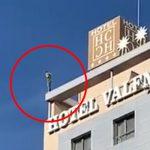 ホテルの屋上から飛び降り自殺する男。