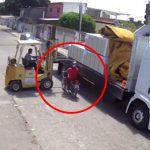 トラックに荷物を積んでいたフォークリフトの隙間を通ろうとしたバイク、転倒してしまう・・・。