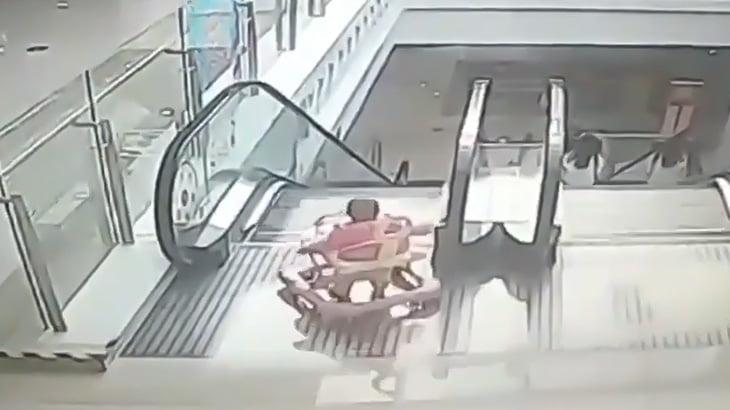 ベビーウォーカーで歩き回っていた赤ちゃん、エスカレーターを降りようとして転倒してしまう映像。