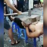 腹の上に置いた石をハンマーで叩き割った瞬間、血を吐き出す映像。