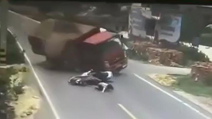 バイク同士の謎の接触事故によりトラックが横転して下敷きになったバイカーが死亡する映像。