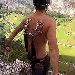 パラシュートのフックを背中に突き刺して崖から飛び降りる男の映像。