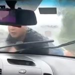 ボンネットに男を乗せたまま高速道路を走る車の映像。
