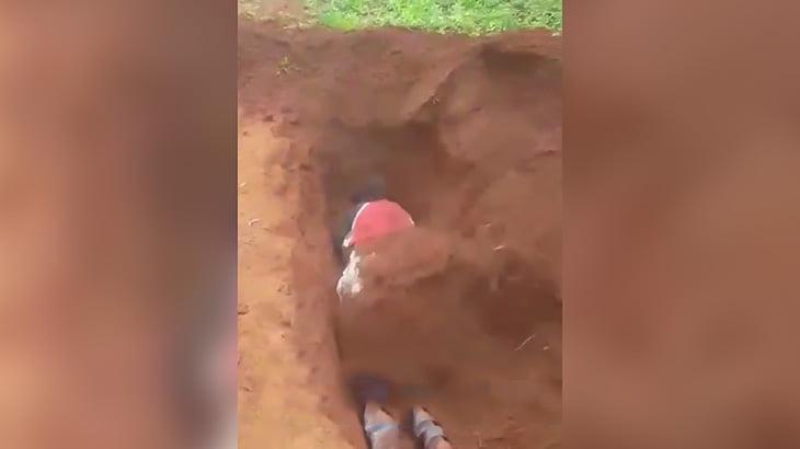 掘った穴にうつ伏せになり、銃殺された後そのまま埋められてしまう女性の映像。