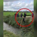 川を長い木の棒で乗り越えようとして落ちてしまう男性の映像。