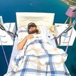 パラグライダーにベッドを付けて空で寝る男の映像。