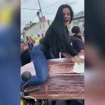 棺桶にまたがってセクシーなダンスを踊る女性の映像。