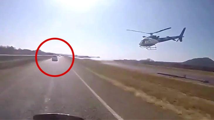 逃走する車を警察のバイクとヘリが追跡する映像。