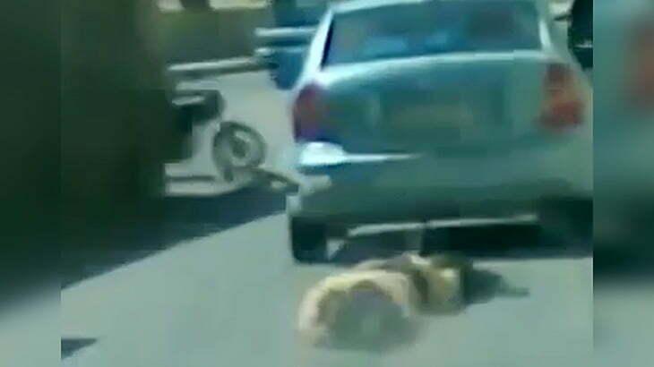 男にロープをくくりつけて車で引きずり回す映像。