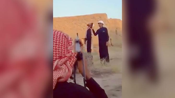 仲間が口に咥えたタバコを銃で撃ち抜く男の映像。