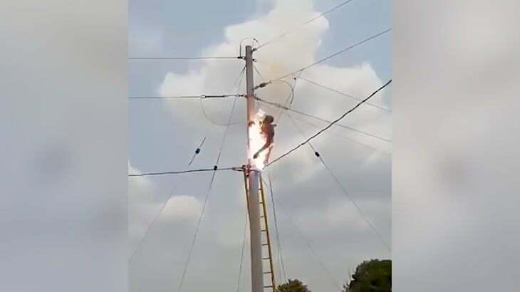 電柱に登った男性が感電して身体から火花があがる映像。