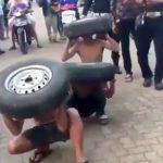 盗みを働いた3人の男たちが罰としてタイヤを持って街を練り歩く刑に処されてしまった映像。