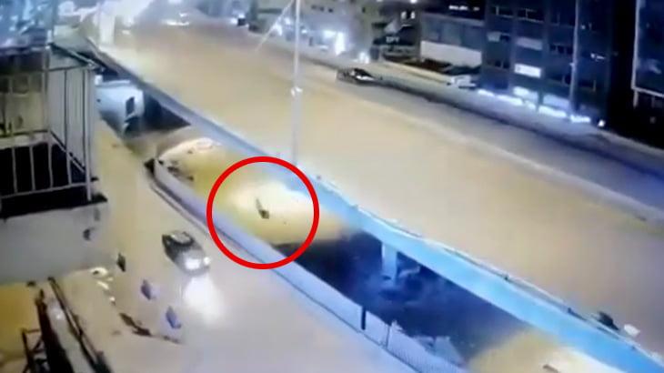 陸橋から転落したバイカーが下を走っていた車に轢かれてしまう映像。