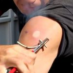 ガスバーナーや熱した鉄で肩にマークを刻む男の映像。
