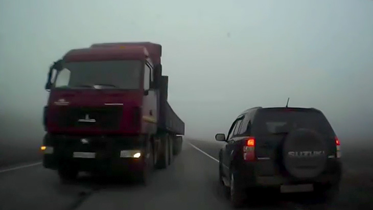 濃い霧に包まれた道路で突然トラックが突っ込んでくる映像。