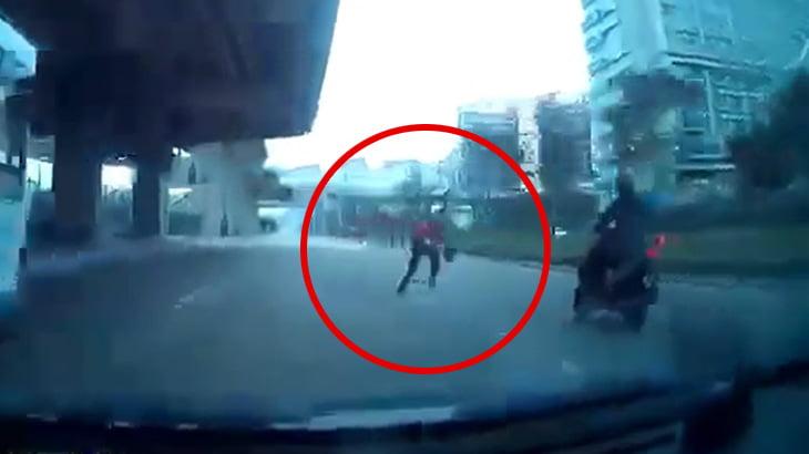 走行中のバイクに一直線に走り寄ってタックルをかます当たり屋の男の映像。