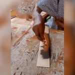 木の板に接着剤を付けて砂をサッと振りかけるだけで顔を描く男の映像。