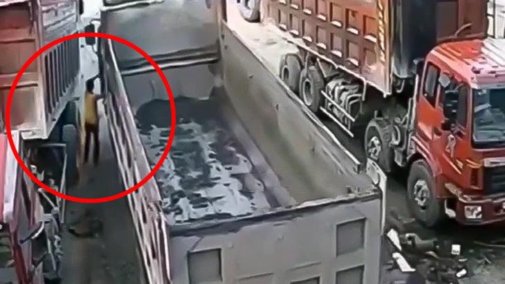 トラックにゆっくり挟まれてしまう男の映像。