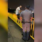 橋から身を投げようとする男を助け出して慰める警察官の映像。