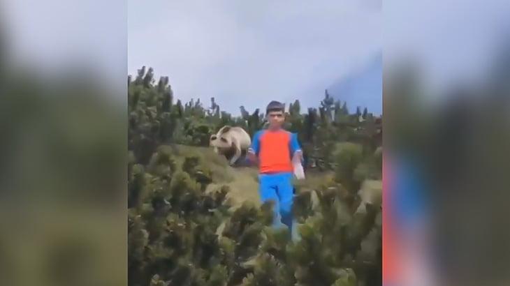 背後から迫りくるクマからゆっくりと逃げる映像。