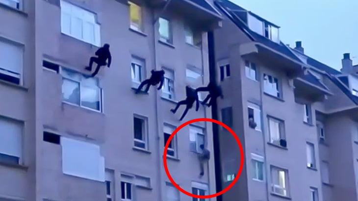 窓から飛び降りようとする男性を屋上からロープで降りて助けようとして失敗する映像。
