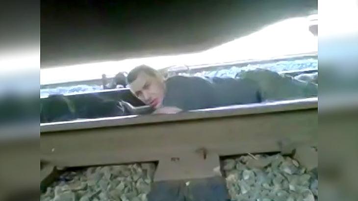 線路にうつ伏せになり通過する電車の隙間を抜けようとする男の映像。