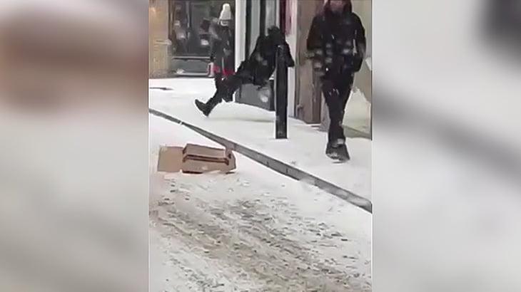 凍った歩道で転倒する人たちを見て大爆笑する男たちの映像。