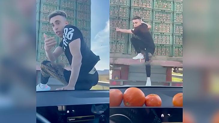 前を走るトラックに乗り移って遊ぶ男の映像。